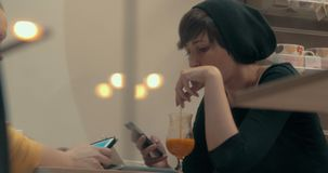 Female friends spending time with mobile and pad during the meeting in cafe stock footage