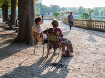 Two women friends chat on park chairs in the Jardin de Luxembour Royalty Free Stock Image