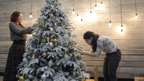 Two women friends decorating Christmas tree at home. Females standing from two sides of pine Asian woman brunette in sweater, brown pants hanging gold silver stock footage