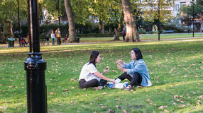 Two women friends eat and chat on lawn in Russell Square, London Stock Photo