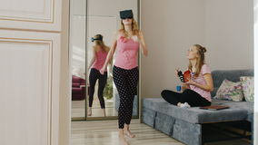 Two women friends have a rest at home. One dancing in the virtual reality helmet, the other eats their food paper box. Pajama party friends. HD video stock footage