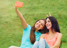 Two women friends having fun and taking pictures of themselves w. Two happy women friends laughing and sharing social media pictures in a smart phone on picnic Stock Photos