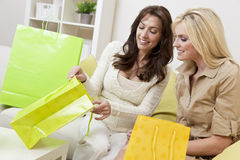 Two Women Friends Looking in Shopping Bags at Home. Two beautiful women friends at home looking in shopping bags together royalty free stock photo