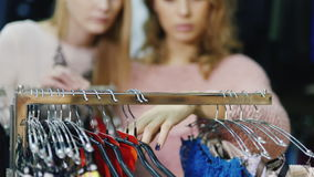 Two women friends looking at the underwear in a clothing store for women. Their faces are blurred in, in the frame. Visible hands that are sorted out a hanger stock video