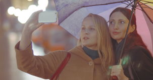 Two women friends making selfie with umbrella on. Two young girls friends with multicolored umbrella have a good time while making selfie on the street on rainy stock footage