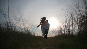 Two women friends running away from camera at sunset. Slow-motion stock video