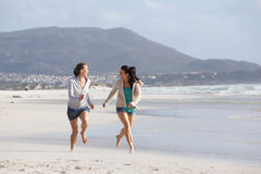 Two women friends running on the beach together. Portrait of two women friends running on the beach together Stock Photos