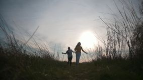 Two women friends running to camera at summer sunset. Slow-motion stock video