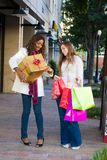 Two Women Friends Shopping. Two attractive young happy women walking in an urban city environment and carrying Christmas gifts Royalty Free Stock Images