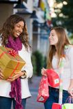 Two Women Friends Shopping. Two attractive young happy women walking in an urban city environment and carrying Christmas gifts Royalty Free Stock Photo