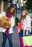 Two Women Friends Shopping. Two attractive young happy women walking in an urban city environment and carrying Christmas gifts Royalty Free Stock Image