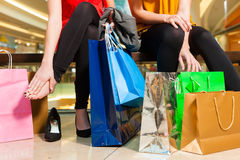 Two women friends shopping in a mall. Two female friends with shopping bags having fun while shopping in a mall, the feet hurt already stock photography