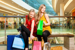 Two women friends shopping in a mall. Two female friends with shopping bags having fun while shopping in a mall, the feet hurt already royalty free stock photography