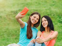 Two women friends smiling and taking pictures of themselves with. Two happy women friends laughing and sharing social media pictures in a smart phone on picnic Stock Image