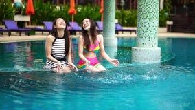 Two women friends splashing water in swimming pool. Slow motion of two women friends splashing water in swimming pool stock video footage