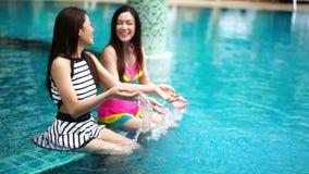 Two women friends splashing water in swimming pool. Slow motion of two women friends splashing water in swimming pool stock video