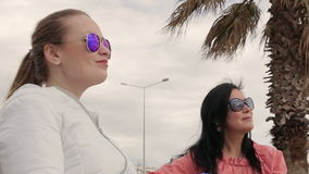 Two women friends in sunglasses of the talking at the bench. Close-up stock footage