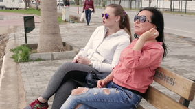 Two women friends in sunglasses of the talking at the bench. stock video