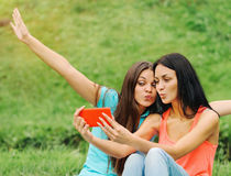 Two women friends taking pictures of themselves with smart phone. Two happy women friends laughing and sharing social media pictures in a smart phone on picnic Stock Images