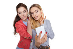 Two women friends taking selfie with smartphone. Royalty Free Stock Images