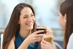 Two women friends talking in a coffee shop. Portrait of two women friends talking holding coffee cups in a restaurant Stock Photos