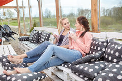 Two women friends talking holding coffee cups Royalty Free Stock Photo