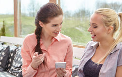 Two women friends talking holding coffee cups Stock Photos