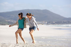 Two women friends walking together on the beach Stock Photos