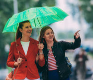 Two women friends walking under umbrella laughing looking at something Stock Image