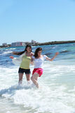 Two women frolicking in the sea. Splashing around in the surf in their shorts as they enjoy their summer vacation Royalty Free Stock Photos