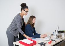 Two women in front of the computer at office Stock Photos