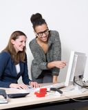 Two women in front of the computer at office. Two business women are sitting/standing in front of the computer in the office. Both women are smiling and looking Stock Photo