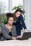 Two women in front of a notebook. Two young business women are sitting/standing in front of a notebook in the office. One women is wearing a headset Stock Photography