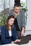 Two women in front of a notebook. Two young business women are sitting/standing in front of a notebook in the office. One women is wearing a headset Stock Photo