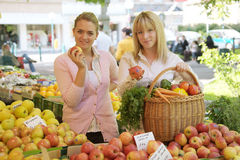 Two women on the fruit market royalty free stock image
