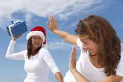 Two women fun with christmas present Stock Photo