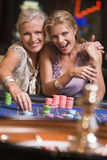Two women gambling at roulette table. In casino royalty free stock images