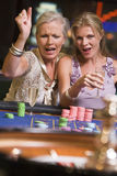Two women gambling at roulette table. In casino royalty free stock photo
