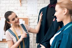 Two women at garment factory desining new man suit jacket. Two women at garment factory desining new men suit jacket. They are happy and fashionable Stock Image