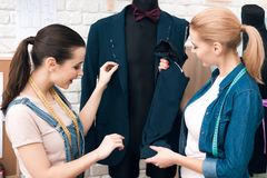 Two women at garment factory desining new man suit jacket. Two women at garment factory desining new men suit jacket. They are happy and fashionable Stock Photo