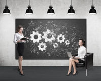 Two women and gears on blackboard. Two women in a room. One is holding a book. The second is sitting with her laptop in an armchair. Gears are drawn on a Royalty Free Stock Images