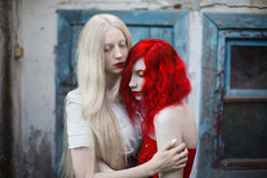 Two women, a girl with curly red hair and a woman with long straight white hair Royalty Free Stock Photo