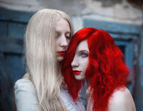 Two women, a girl with curly red hair and a woman with long straight white hair. Two women, a girl with curly red hair and a women with long straight white hair Stock Images
