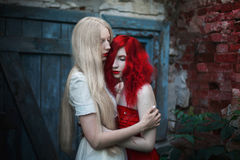 Two women, a girl with curly red hair and a woman with long straight white hair. Two women, a girl with curly red hair and a women with long straight white hair Royalty Free Stock Images