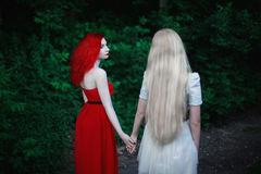 Two women, a girl with curly red hair and a woman with long straight white hair Stock Image