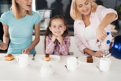 Two women and a girl getting ready to drink tea with a homemade pie in their kitchen Royalty Free Stock Photography
