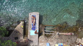 Two women and a girl sunbathing on dock. SOLTA, BRAC - JULY 2014: Woman in bikini and a girl lying on a towel sunbathing, Croatia stock video footage