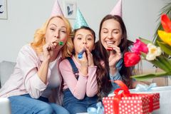 Grandmother mother and daughter together at home birthday sitting blowing party horns playful royalty free stock photos