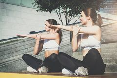 Two women, girls in sportswear doing stretching exercises while listening to music. Workout, couching on city street. Royalty Free Stock Photo