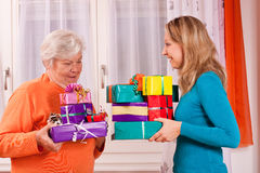 Two women are giving gifts to each other Stock Photos